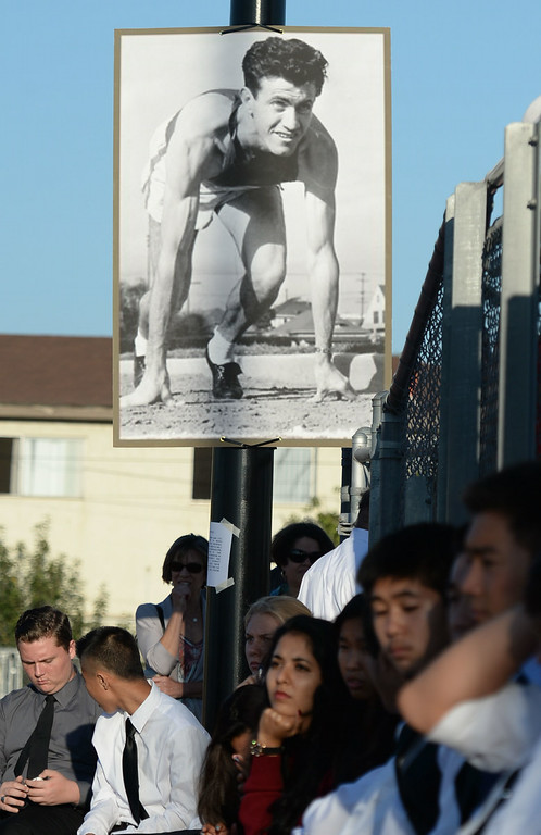 . A picture of Louis Zamperini as a track runner hangs over the crowd at a memorial for the Torrance legend, who died earlier this month Thursday, July 31, 2014, Torrance, CA.  Zamperini was an Olympian, WWII bomber pilot and Japanese POW. A book by Laura Hildebrand titled Unbroken documented his life and a movie directed by Angelina Jolie will be released in December. Photo by Steve McCrank/Daily Breeze