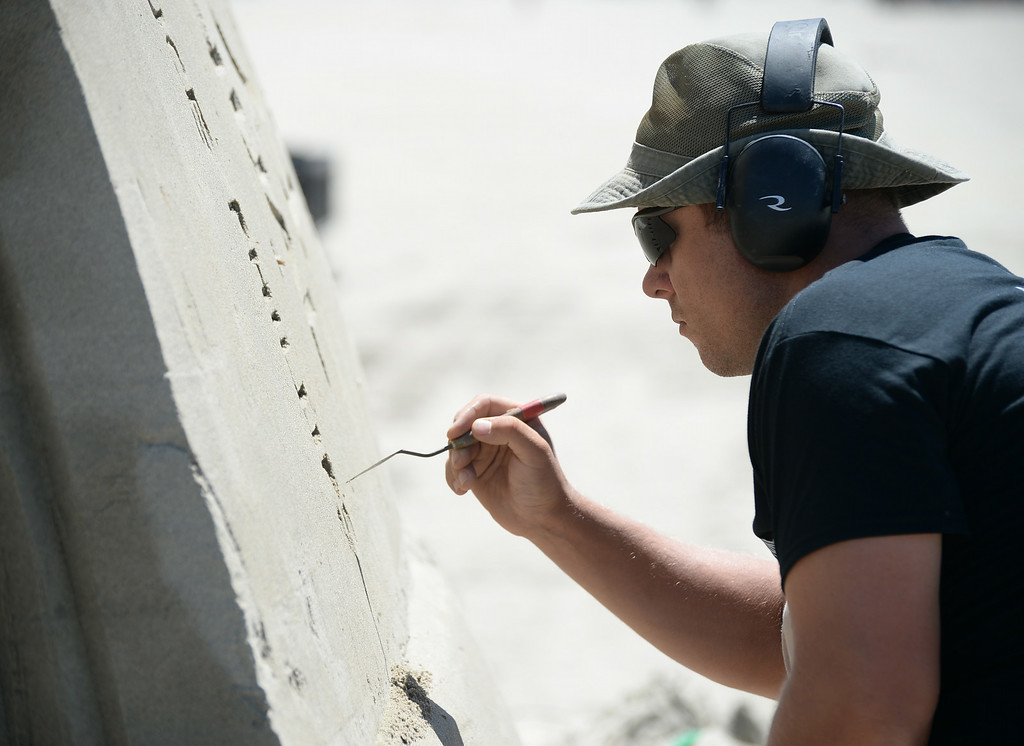 . Artists took to the beach at Belmont Shore for the 82nd Annual Sand Sculpture Contest Saturday, August 16, 2014, Long Beach, CA.   Sandis Kondrats adds details. Photo by Steve McCrank/Daily Breeze