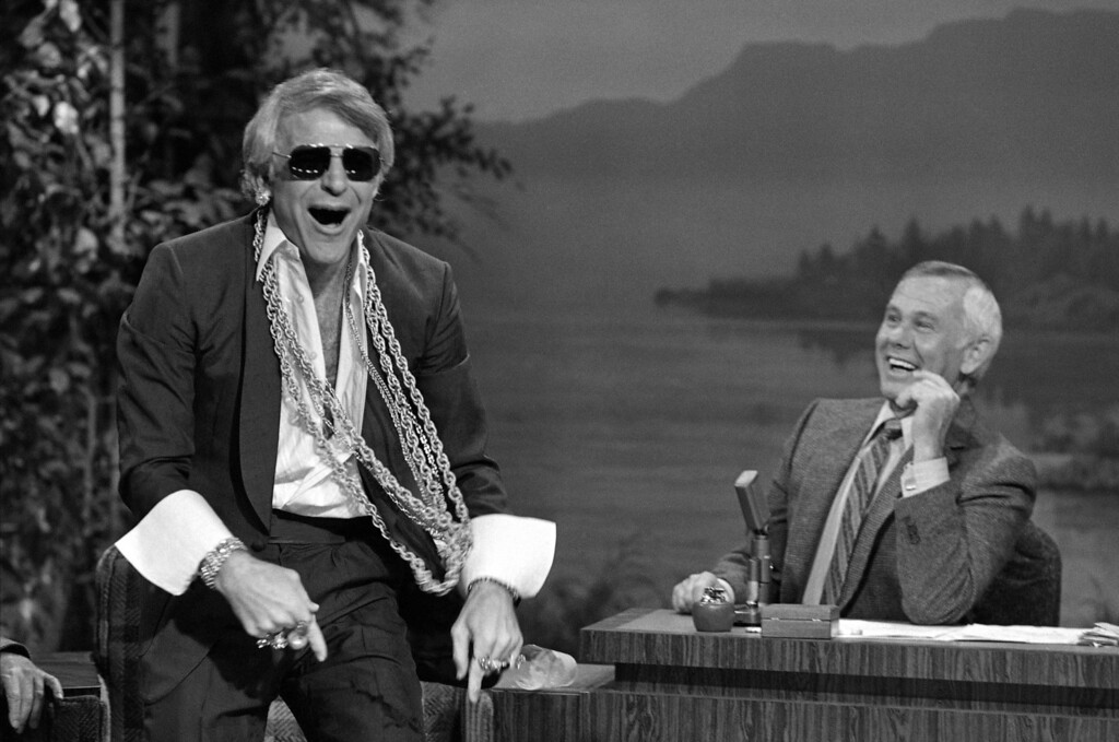""". Comedian Steve Martin left, festooned with mock jewelry and other ornaments, entertains Tonight show host Johnny Carson during a taping of the show at NBC studios in Burbank Calif., July 19, 1980.  Martin,  a surprise guest on the show, playfully answered the question, \""""Has success spoiled Steve Martin?\"""" by showing up in chains, rings and earrings, and throwing fistfulls of \""""money\"""" at Carson, who was making his first Tonight Show appearance since he underwent surgery on his leg last week. ( AP Photo/Lennox McLendon)"""
