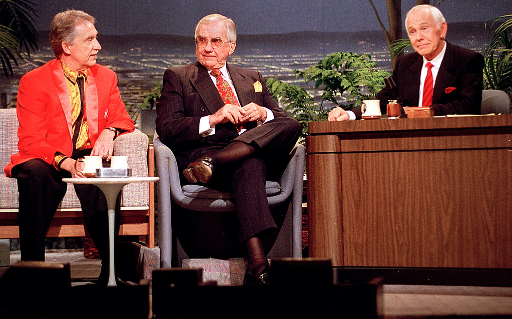 """. FILE - In this Friday, May 22, 1992 file photo, talk show host Johnny Carson, behind his desk, Doc Severinsen, left, leader of \""""The Tonight Show Band\"""", and announcer Ed McMahon, center, share some moments together during the final taping of the \""""Tonight Show\"""" in Burbank, Ca. McMahon, the loyal \""""Tonight Show\"""" sidekick who bolstered boss Johnny Carson with guffaws and a resounding \""""H-e-e-e-e-e-ere\'s Johnny!\"""" for 30 years, has died at a Los Angeles hospital. He was 86. (AP Photo/Douglas C. Pizac, File)"""