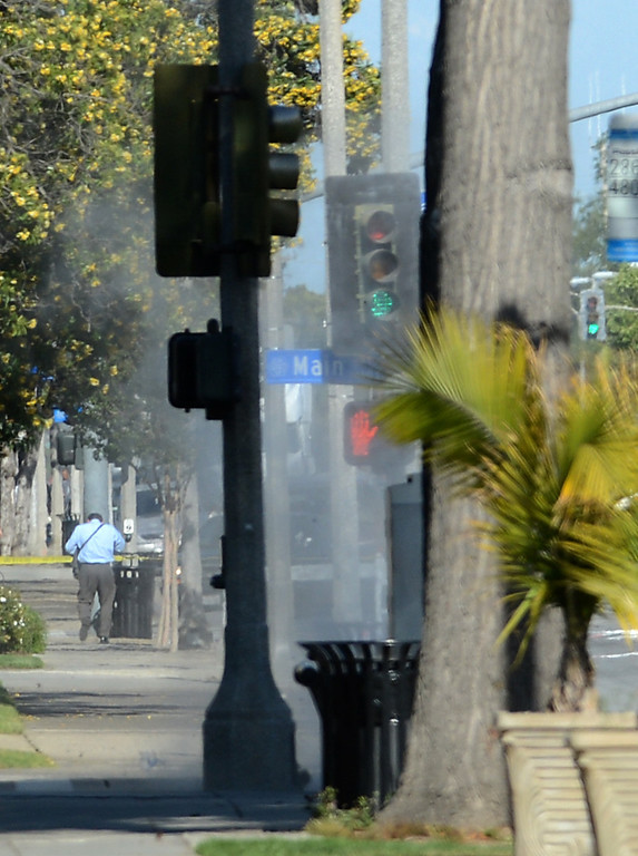 . A pedestrian runs away as the LA County Sheriff\'s Bomb Squad detonates a suspicious package Thursday, April 18, 2013, at the corner of W Mission Blvd and S Main Street in Pomona. Jennifer Cappuccio Maher/Staff Photographer