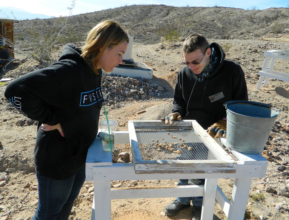 Description of . Archaeologist and volunteer Michelle Nagy, left, helps a volunteer in a class at the Early Man Site near Yermo, CA, Jan. 4, 2014. The class teaches how to carefully clear an area in search for relicts from early man.  Once cleared, the sand and rocks are sent through a screen to make sure nothing important has been missed. (Photo by Joe Blackstock/Staff)