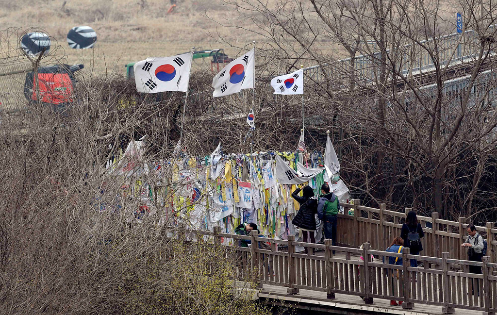 ". South Korean national flags flutter on a wire fence, where ribbons are hanging with messages wishing for reunification of the two Koreas, at the Imjingak Pavilion near the border village of Panmunjom, dividing the two Koreas since the Korean War, in Paju, north of Seoul, South Korea, Friday, April 5, 2013. After a series of escalating threats, North Korea has moved a missile with ""considerable range\"" to its east coast, South Korea\'s defense minister said Thursday. But he emphasized that the missile was not capable of reaching the United States and that there are no signs that the North is preparing for a full-scale conflict. (AP Photo/Lee Jin-man)"