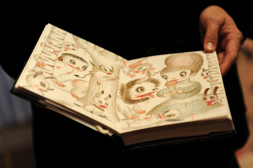 . Gary Baseman shows one of the sketch books he always carries with him. (Michael Owen Baker/Staff Photographer)