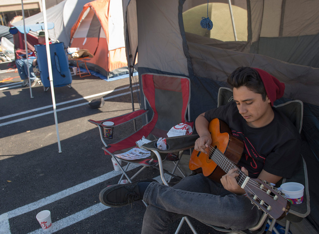 . Chick-fil-A contestant Louis Garcia, 19, of Walnut passes time strumming guitar while camping out at the company\'s new Azusa location to receive 52 free-meal coupons Feb. 20, 2013.  Contestants waiting for the day and staying overnight are treated to games and free meals.  (SGVN/Staff photo by Leo Jarzomb)