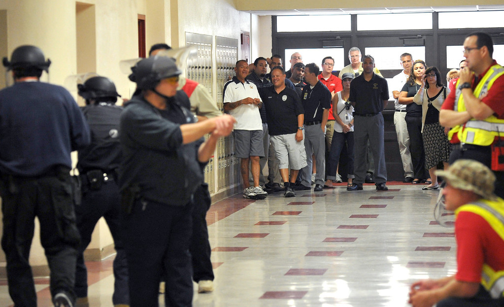 . Whittier Union High School District administrators and security officers observe as Whittier Police Officers participate in Active Shooter Scenario training in a hallway at Whittier High School on Tuesday July 23, 2013. The department is putting all 120 of its officers throug three different scenarios during the two-days of training at the high school. (SGVN/Staff Photo by Keith Durflinger)