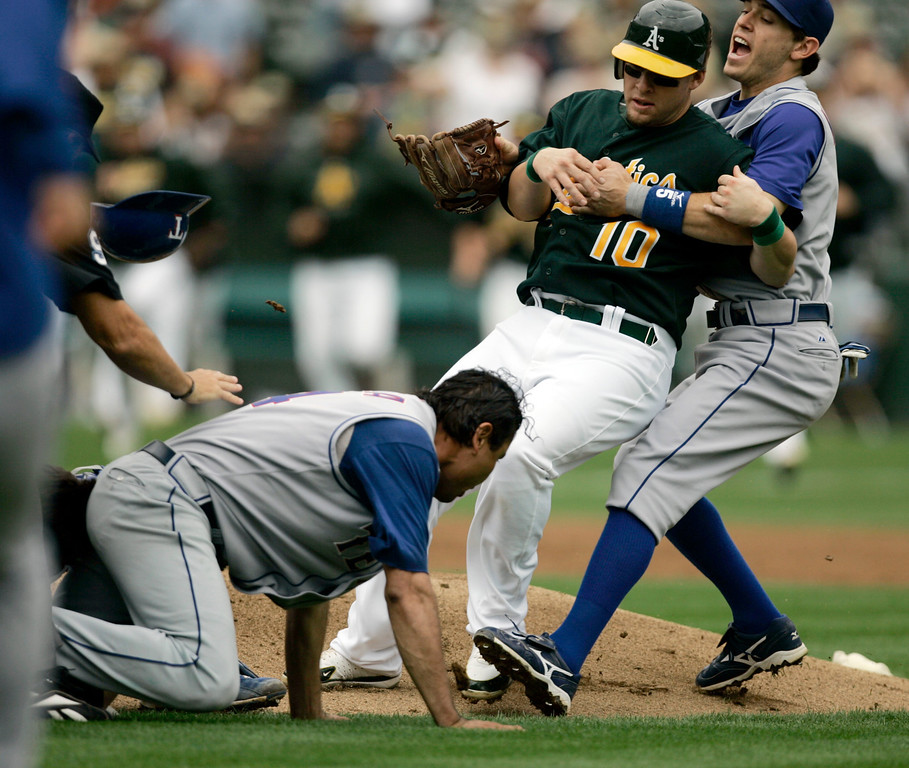 . Oakland Athletics\' Daric Barton (10) is restrained by Texas Rangers second baseman Ian Kinsler, right, as Rangers pitcher Vicente Padilla crawls away during a bench-clearing brawl in the first inning of a baseball game Sunday, Sept. 16, 2007, in Oakland, Calif.The fight was sparked when Padilla hit Nick Swisher in the ribs on a full count. Swisher rushed the mound and tackled Padilla, prompting both benches to rush onto the field. Padilla and Swisher were both ejected. (AP Photo/Ben Margot)