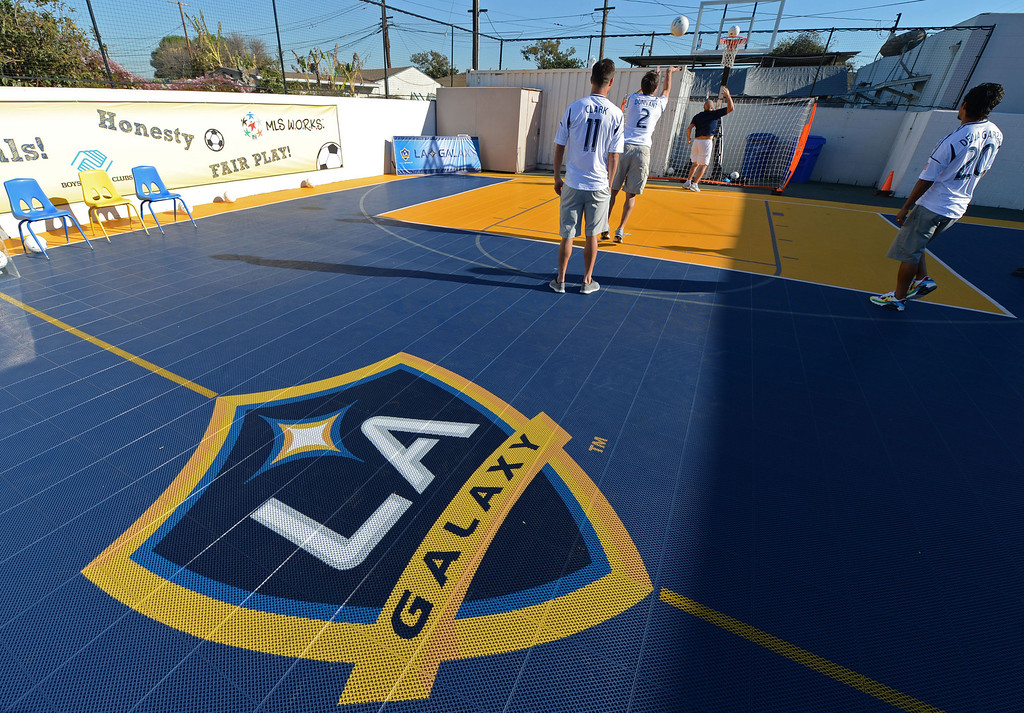 . The L.A. Galaxy unveiled a new Sport Court at the Boys and Girls Club of Carson Friday. In December, with the team heading to the championships, the LA Galaxy Foundation announced it would put in the court, donate equipment and host clinics.  Team players Colin Clark (11), A.J. De La Garza (20), and Todd Dunivant (2) use the new court to shoot some hoops, with soccer balls, before the unveiling ceremony. 20130301 Photo by Steve McCrank / Staff Photographer