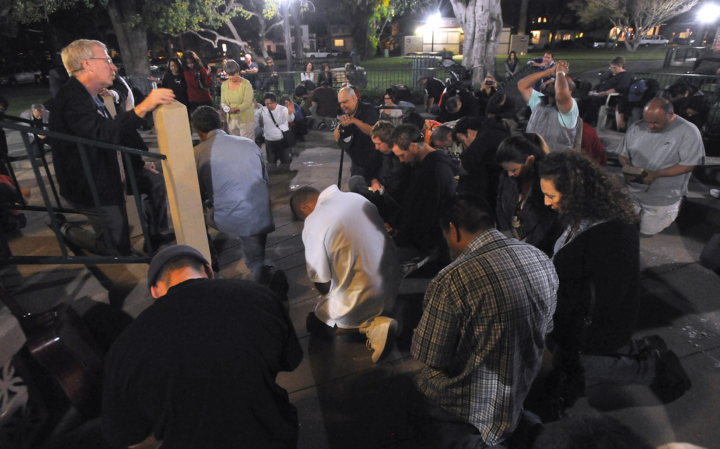 . Councilmember Joe Vinatieri leads a prayer as residents gather for a community-wide prayer vigil at Central Park in Whittier in response to recent attempted child abductions on Friday March 15, 2013. About 150 people attended the candlelight vigil led by Pastor Sam Gamboa of the Good Shepherd Family Bible Church and organized by the Whittier Area Evangelical Ministerial Alliance. City and police officials joined citizens and area church members as they prayed for protection of the children and the arrest of the suspects. (SGVN/Staff Photo by Keith Durflinger)