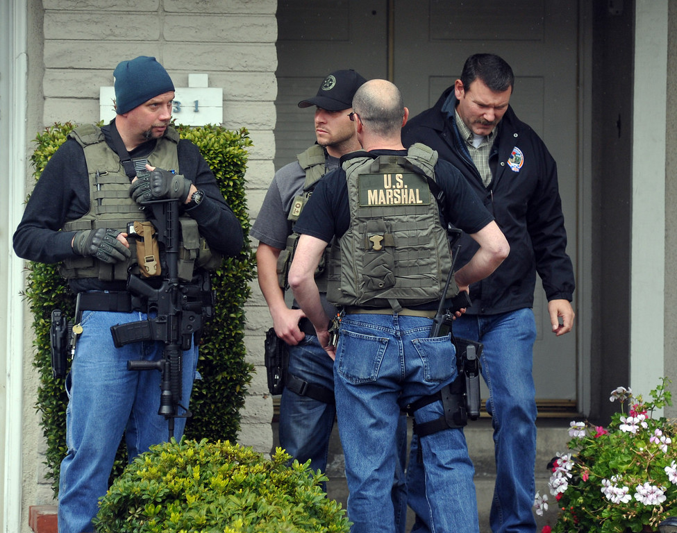 . U.S. Marshals and La Palma Police stand with weapons ready outside of what is believed to be Christopher Dorner\'s mother\'s La Palma home as FBI computer recovery task force investigators armed with a search warrant go through a computer at the home on Friday February 8, 2013. Various agencies have arrived to lend assistance at the home. (SGVN/Staff Photo by Keith Durflinger)