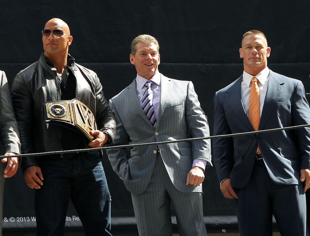 . This image released by Starpix shows actor and WWE star Dwayne Johnson, better known as The Rock, left, with Vince McMahon, and WWE star John Cena at a news conference at Radio City Music Hall in New York on Thursday, April 4, 2013.  Johnson and Cena will face off in the ring at Wrestlemania 29 on Sunday, April 7, at at MetLife Stadium in East Rutherford, N.J.  (AP Photo/Starpix, Dave Allocca)