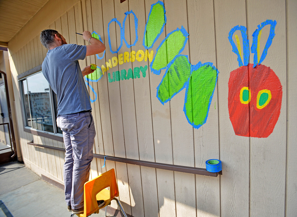 . 03-16-2013--(LANG Staff Photo by Sean Hiller)- Volunteers and students help the Anderson Elementary School Library sort and process new and donated books as well as spiff up campus with some colorful murals at Saturday\'s event organized by Access Books. Bryan De Roo, a parent of a student at Westland School in Los Angeles, helps paint a mural outside the Anderson Library.
