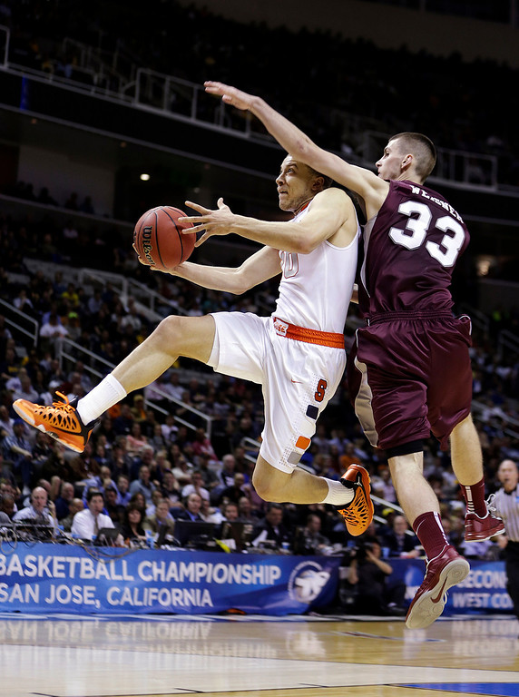 . Syracuse guard Brandon Triche (20) is fouled by Montana forward Mike Weisner (33) during the first half of a second-round game in the NCAA college basketball tournament in San Jose, Calif., Thursday, March 21, 2013. (AP Photo/Ben Margot)