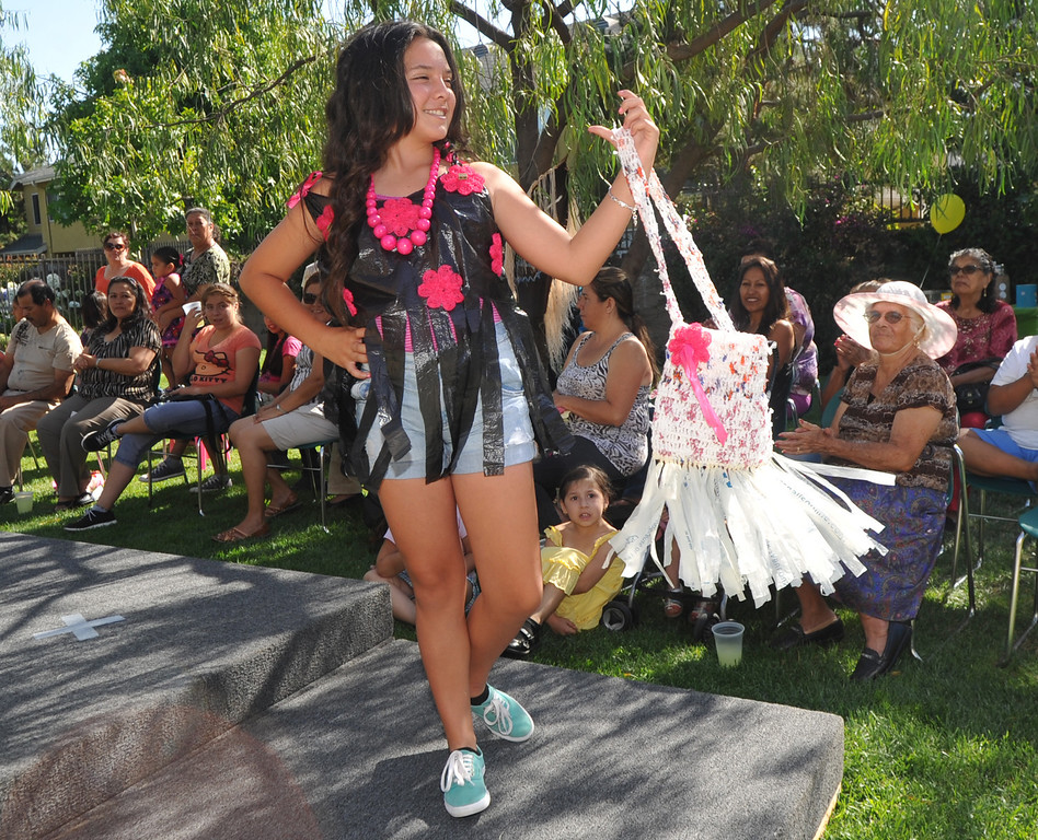 Description of . Andrea Lopez, 13, shows her trash bag blouse with recycled flowers and a crocheted plastic purse in the