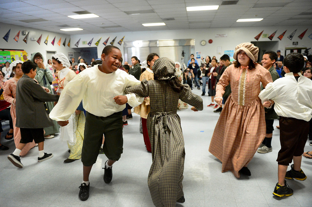 Description of . Tracy Elementary School fifth-graders do the Virginia Reel during a Colonial Festival Tuesday morning, March 26, 2013 at the Baldwin Park school. In one month the students completed a report, learned two songs and two dances. Grecia Herrera, the school's nutritional aid, made the dresses and boys' suits. (SGVN/Staff Photo by Sarah Reingewirtz)