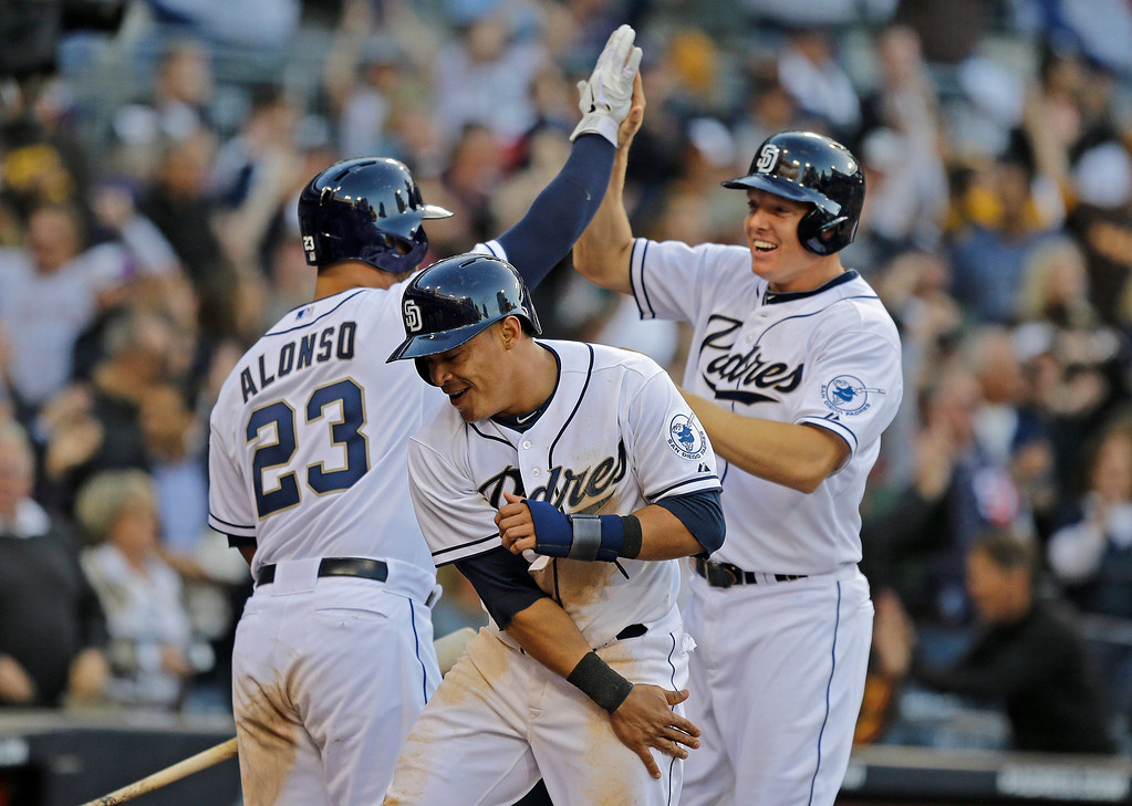 . San Diego Padres\' Everth Cabrera, center,  Nick Hundley, right, and Yonder Alonso celebrate after a bases loaded triple by teammate Will Venable during the eighth inning of a baseball game in San Diego, Tuesday, April 9, 2013. (AP Photo/Lenny Ignelzi)