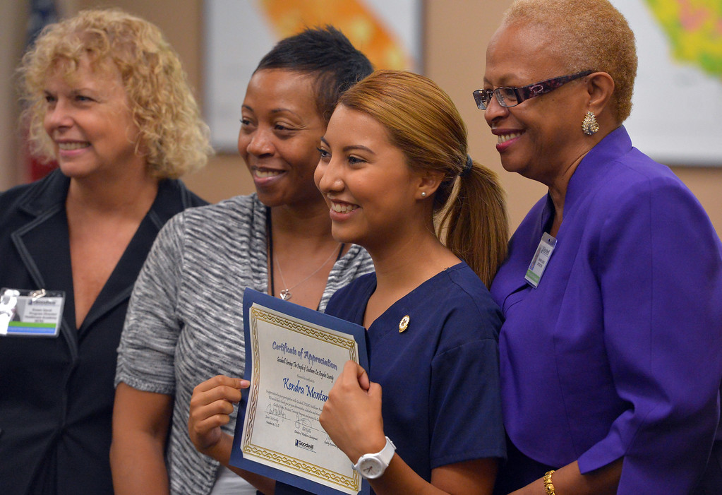 . Kendra Montano stands with teachers and Goodwill staff as she and nine other recent high school graduates received their Certified Nursing Assistant certificates at the Goodwill in Long Beach, CA on Friday, August 22, 2014. The students; Gabriela Avila, Averianna Burnett, Alesia Clay, Ariana Mays, Kendra Montano, Silvia Monzon, Genesis Perez, Cindia Sanchez, Daniel Scott and Dahlia You completed the year-long course in a partnership between the LBUSD and Goodwill. This is the first year that the state Certified Nurse Assistant Training Academy program has been free for the students. It was announced to the families and friends gathered that all 10 of the graduates have health care job interviews next week. (Photo by Scott Varley, Daily Breeze)