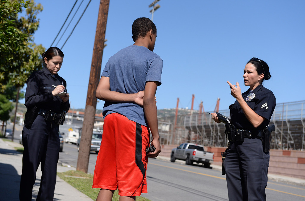 . LAPD officers Melissa Mendoza, left, and Karena Rowan talk to a student who said he overslept and was on his way to class. Operation Back in School picked up dozens of high school age kids that were truant from school. Photo by Brad Graverson 4-10-13