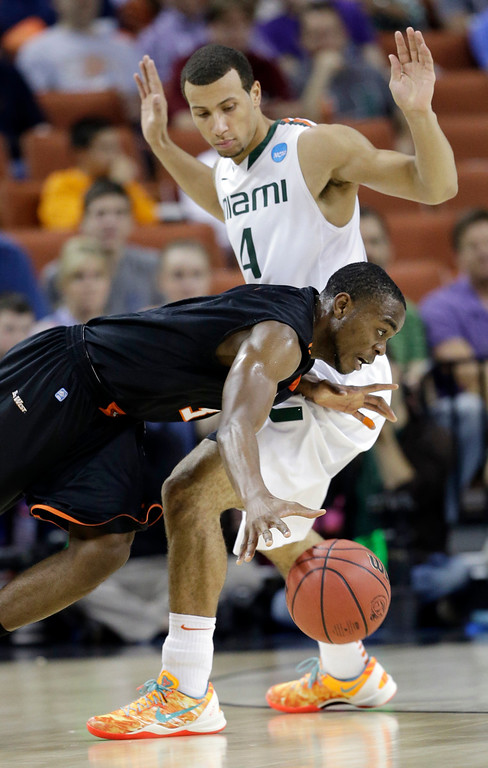 . Pacific\'s Sama Taku tries to drive past Miami\'s Trey McKinney Jones (4) during the first half of a second-round game of the NCAA college basketball tournament Friday, March 22, 2013, in Austin, Texas.  (AP Photo/David J. Phillip)