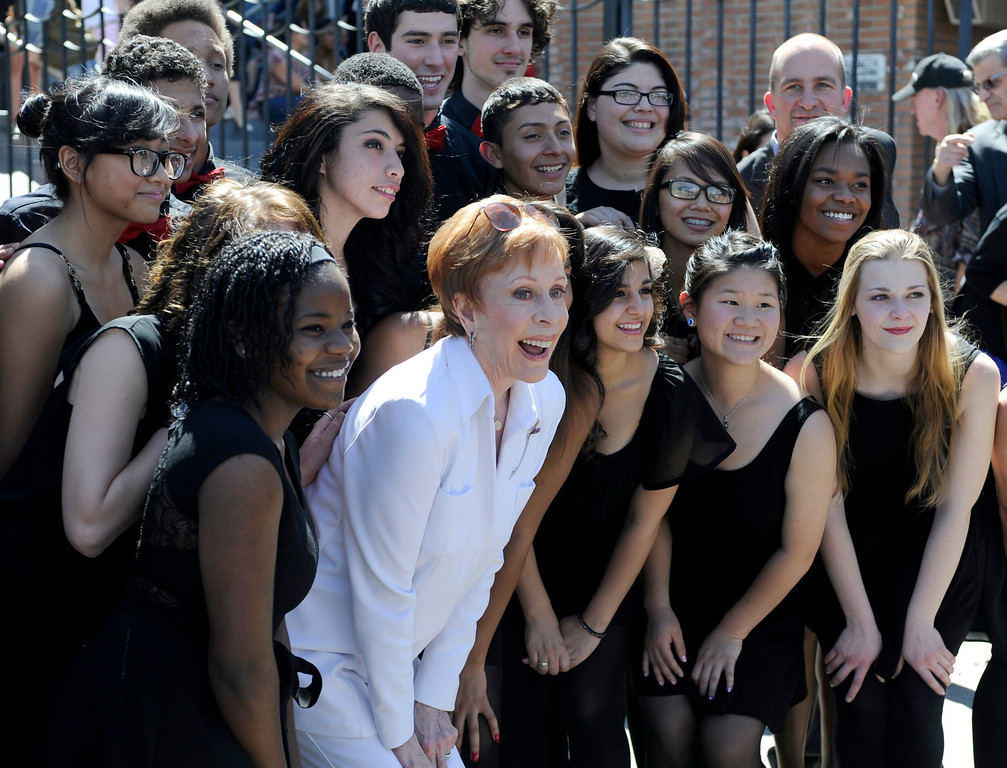". Carol Burnett poses for photos with the Hollywood High School choir H2O. Burnett, award-winning actress, comedienne and best-selling author, was honored by the City of Los Angeles for her lifetime achievements with the naming of Carol Burnett Square at the intersection of Highland Avenue and Selma Avenue. The Square is adjacent to Hollywood High School where Burnett attended. Students from the school choir, ""H2O\"" sang �I�m so glad we had this time together,� before Burnett and LA City Councilman Tom LaBonge unveiled her street sign. Hollywood, CA 4/18/2013(John McCoy/Staff Photographer"