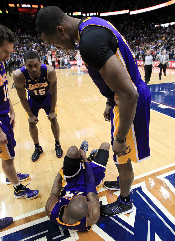 . Los Angeles Lakers\' Dwight Howard leans over teammate Kobe Bryant lays on the floor after being injured in the final seconds of an NBA basketball game against the Atlanta Hawks on Wednesday, March 13, 2013, in Atlanta. The Hawks defeated the Lakers 96-92.  (AP Photo/Atlanta Journal-Constitution, Curtis Compton)