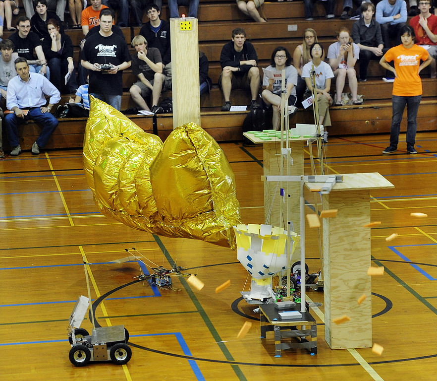 ". Team: Spongebot MetalPants sweeps sponges off a podium into their robot basket for big time score during competition at 28th Annual ME72 Engineering Design Contest, ""Sponge Wars Attack of the Drones\"" at Caltech Brown Gym Tuesday, March 13, 2013. Mechanical Engineering 72 competition features teams maneuvering kitchen sponges into a goal with a pair of autonomous robotic vehicles � and preventing opposing teams from doing the same. Six teams  competed head-to-head in a series of rounds. The team with the most points at the end of each heat wins. The victors earn the admiration of the crowds in the stands and are honored with the ME-72 trophy. (Photo by Walt Mancini/SXCity)"