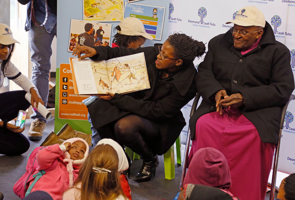 . Archbishop Desmond Tutu, right, looks at pictures in a book, left, after he read to  children  during celebrations for the late South African President Nelson Mandela�s  birthday in Cape Town, South Africa, Friday, July 18, 2014.  (AP Photo/Schalk van Zuydam)