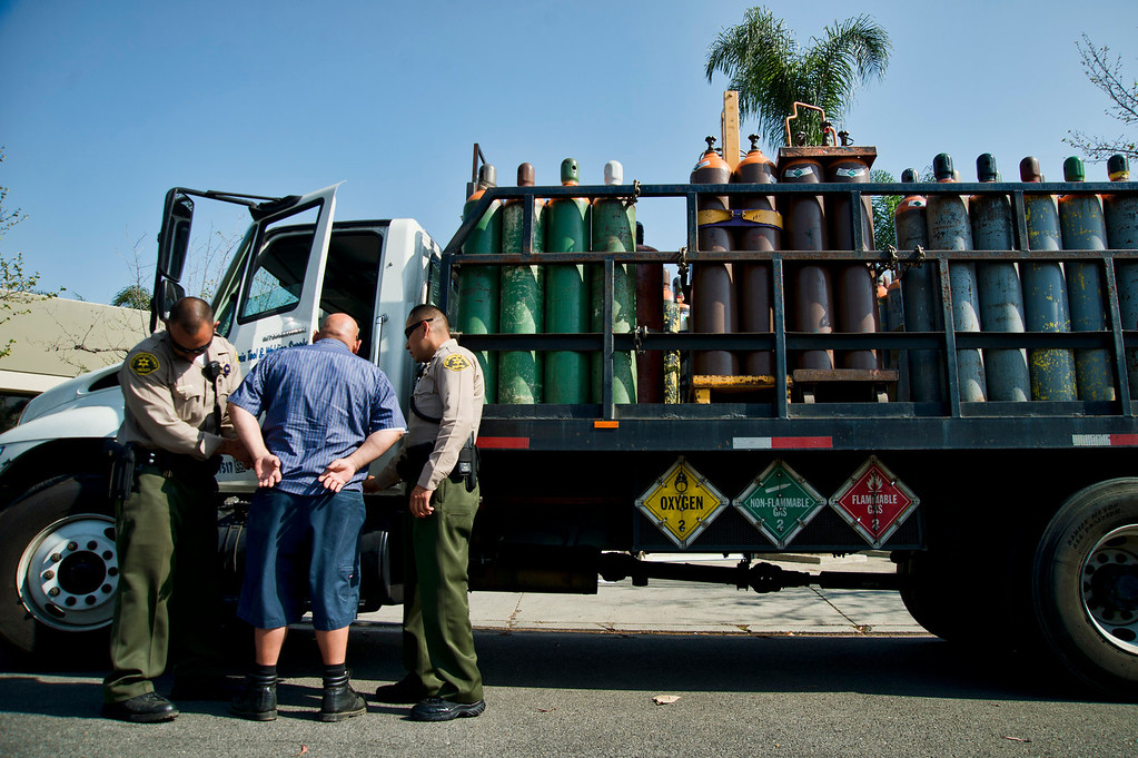 Description of . Los Angeles County Sheriff's deputies detain the deliver driver as he prepares to deliver a truck full of nitrous oxide to auto parts dealer, L.A. Rush, during a search warrant in Norwalk on Friday, March 22, 2013. The business is suspected of illegally selling nitrous oxide for recreational drug use. (SGVN/Staff photo by Watchara Phomicinda)
