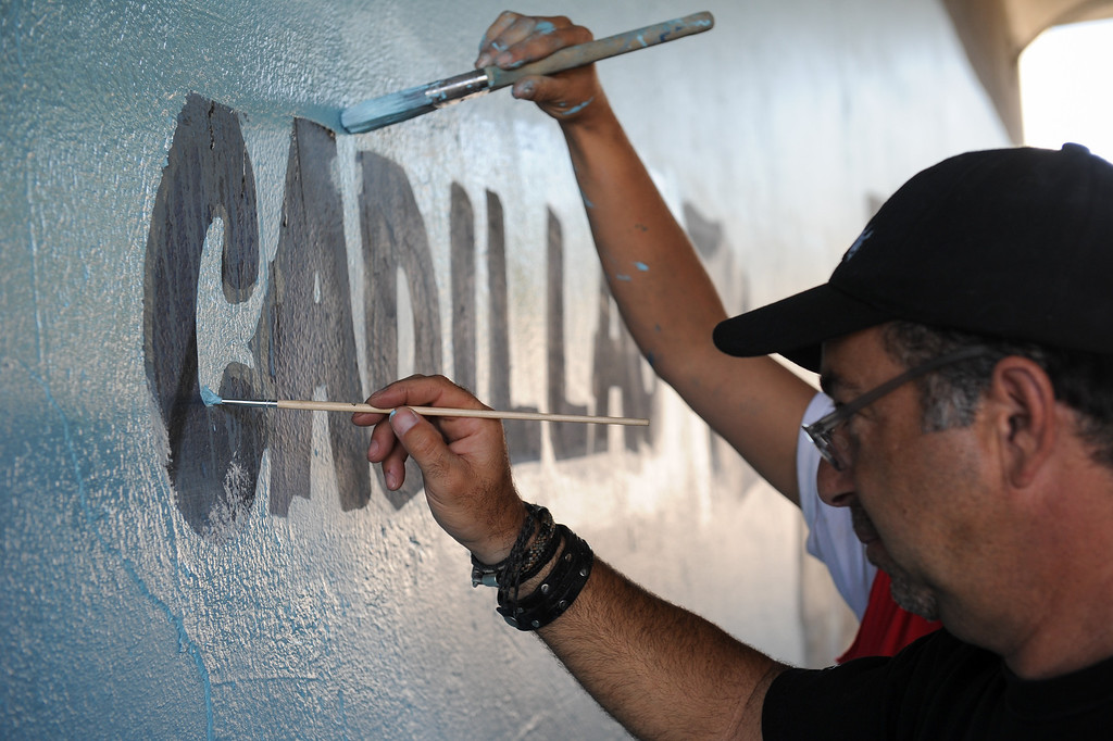 ". Joe Nicoletti paints during the restoration of the mural ""Panorama: G.M. Recollections from the Past,\"" on Van Nuys Boulevard in Panorama City, Thursday, June 20, 2013. The original mural was painted by Alfredo Diaz Flores in 1998 and pays homage to the General Motors plant that used to be near the mural site. (Michael Owen Baker/Staff Photographer)"