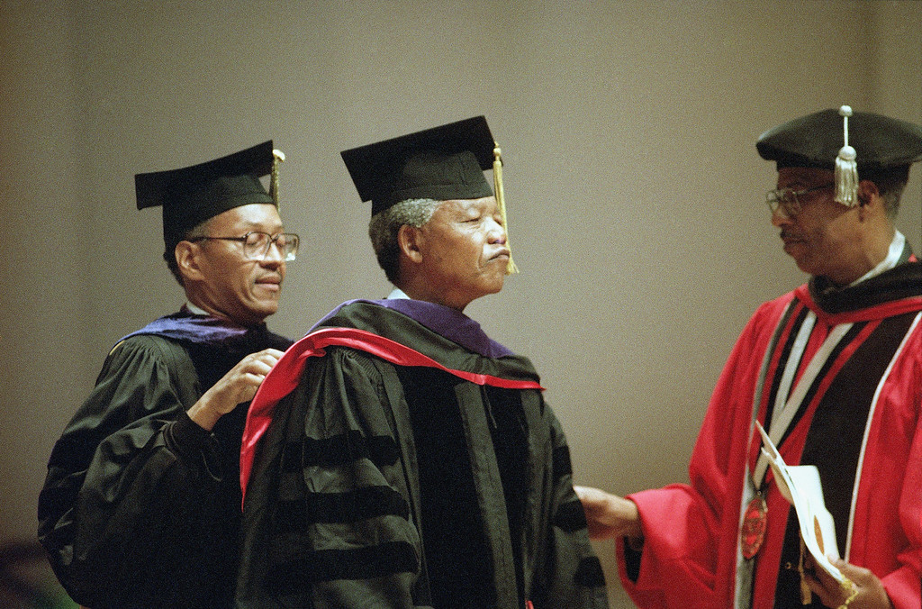. Dr. Earle D. Clowney, left, of Clark Atlanta University, adjusts the hood denoting an honorary doctor of laws degree around African National Congress leader Nelson D. Mandela in Atlanta Sunday, July 11, 1993.  Man at right is unidentified. (AP Photo/Joe Holloway Jr.)