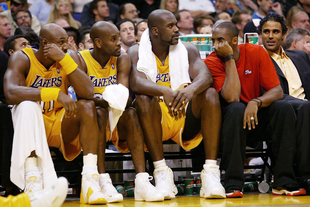. Los Angeles Lakers Kobe Bryant, second right, makes a face at Karl Malone, far left, as teammates Gary Payton, second left, Shaquille O\'Neal, center, and Rick Fox, right, look on during the fourth quarter  against the Dallas Mavericks Tuesday, Oct. 28, 2003, at the Staples Center in Los Angeles. Kobe, who is nursing an injured knee, joined his teammates on the bench in the second half. (AP Photo/Kevork Djansezian)
