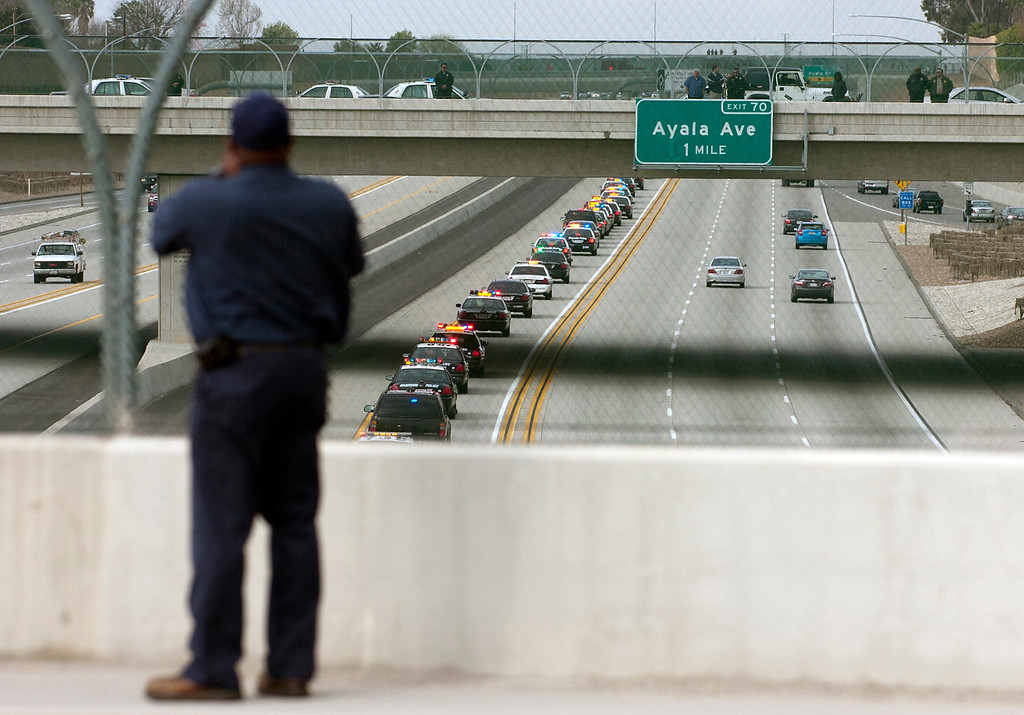 . BN22-MACKAY-FUNERAL-01-JCM (Jennifer Cappuccio Maher/Staff Photographer) A pedestrian stops to watch the funeral procession for San Bernardino County Sheriff\'s Detective Jeremiah MacKay as it heads westbound on the 210 freeway Thursday, February 21, 2013, in Rialto.