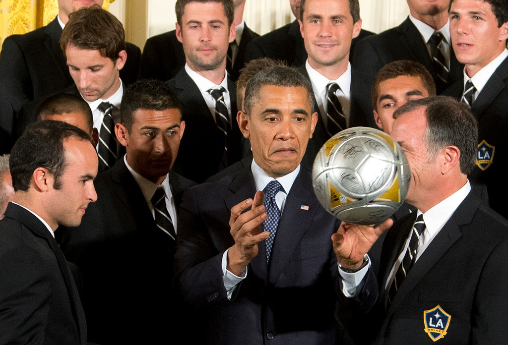 . President Barack Obama, center, flanked by LA Galaxy forward Landon Donovan, left, and coach Bruce Arena, right, throws the soccer ball to the crowd during a ceremony in the East Room of the White House in Washington, Tuesday, March 26, 2013, honoring the Stanley Cup hockey champion Los Angeles Kings and the Major League Soccer champion LA Galaxy for their 2012 championship seasons.   (AP Photo/Manuel Balce Ceneta)