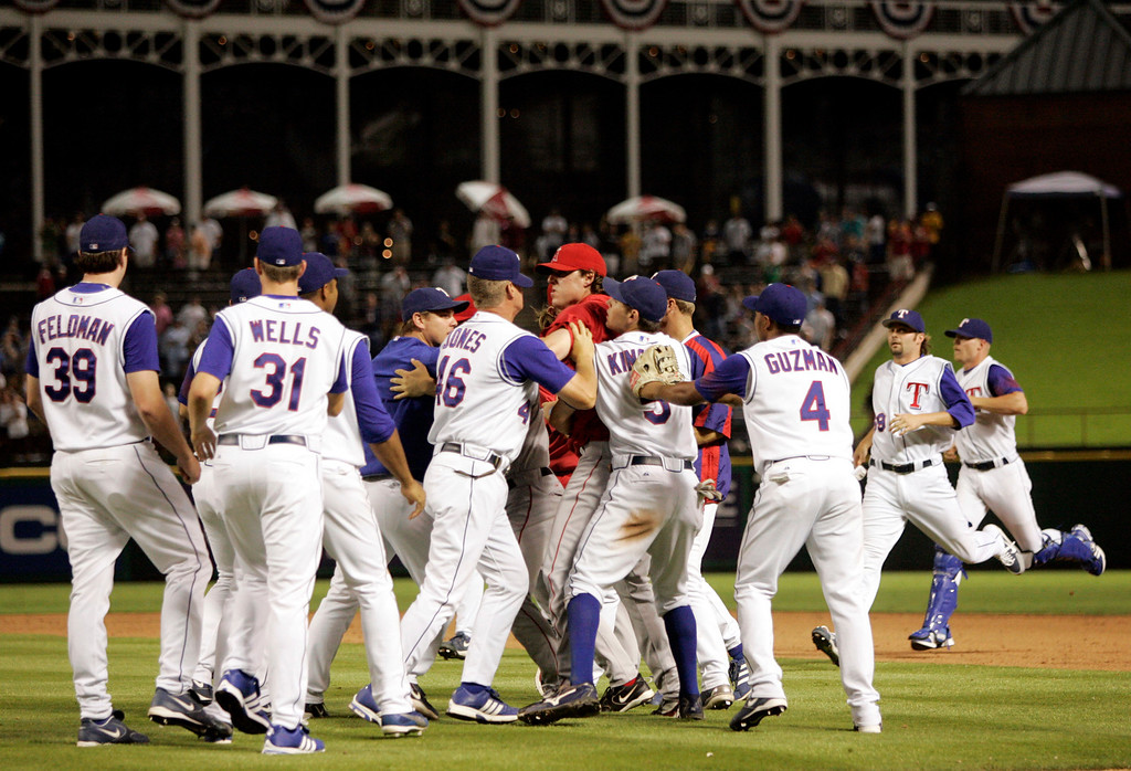 . Texas Rangers players restrain Los Angeles Angels\' John Lackey , center in red, during a brawl after Angels\' Adam Kennedy was hit by a pitch from Scott Feldman in the ninth inning of a baseball game in Arlington, Texas, Wednesday, Aug. 16, 2006. Both Feldman and Kennedy were ejected. The Rangers won 9-3. (AP Photo/Tony Gutierrez)