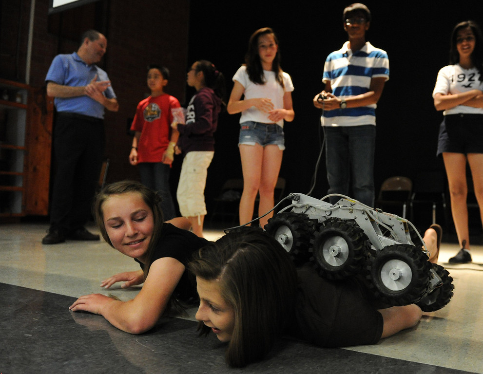 Description of . (John Valenzuela/Staff Photographer)   Eighter grader Tiffiany Renken (left) watches as Anee Patnam controls a small robotic rover as it drive over Ciera Hammond (left) and Maddie Palmer (right) at Cope Middle School in Redlands, Friday , April 19, 2013.  Brian Cooper, lead rover driver of Curiosity and the worlds first Mars rover driver, spoke to eight graders at the middle school about his mulitple missions to Mars.