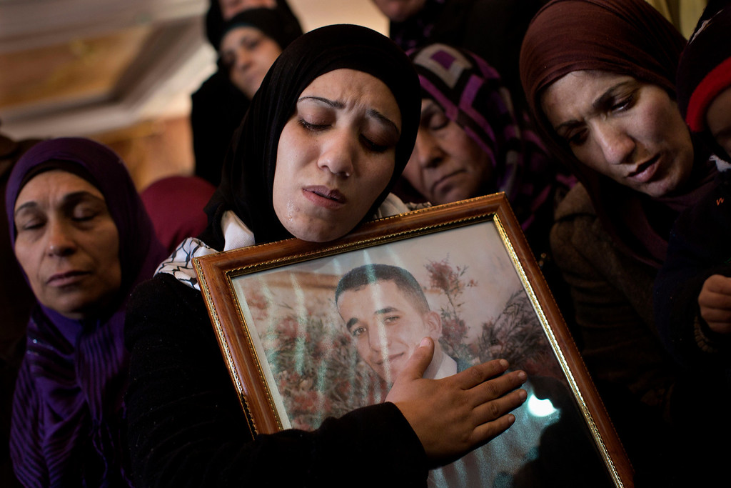 . Palestinian women mourn during the funeral of Arafat Jaradat in the West Bank town of Saeer, near Hebron, Monday, Feb. 25, 2013. Thousands have attended the funeral procession of a 30-year-old Palestinian man who died under disputed circumstances in Israeli custody. Palestinian officials say autopsy results show Jaradat was tortured by Israeli interrogators, while Israeli officials say there\'s no conclusive cause of death yet and that more tests are needed. (AP Photo/Bernat Armangue)