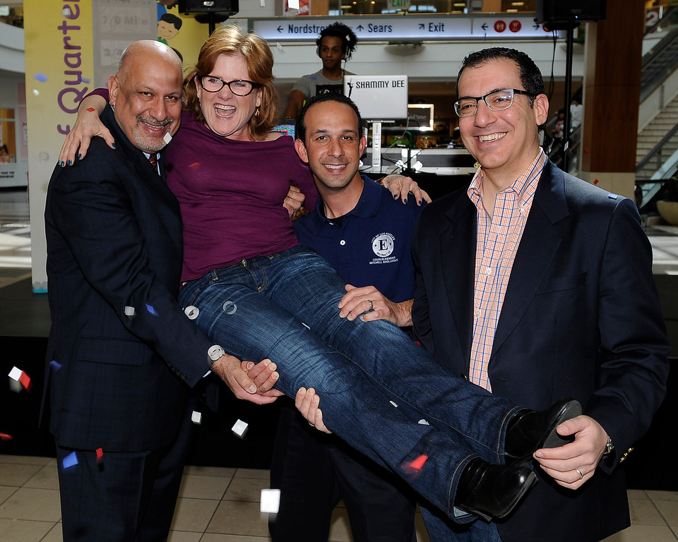 . Nancy Cartwright, one of the event sponsors, is held up by LA City Councilmen Dennis Zine and Mitch Englander with an assist from Assemblymember Bob Blumenfield. The 6th Annual Mile of Quarters event was held at Westfield Topanga Mall to benefit the Boys and Girls Club of the West Valley. The quarters were laid out on the floor on specially marked carpet, with one square foot equaling $3.25. When the entire mile of quarters is completed, $17,160 will be laid out on the floor. Woodland Hills, CA 2/23/2013(John McCoy/Staff Photographer)
