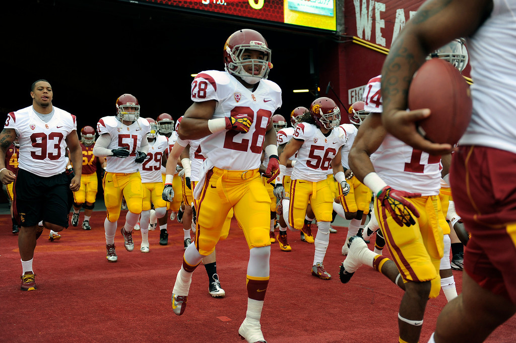 . USC runs onto the field for their Spring Football Game, Saturday, April 13, 2013, at the L.A. Memorial Coliseum. (Michael Owen Baker/Staff Photographer)