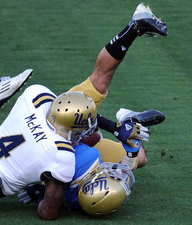 Description of . UCLA tight end Grayson Mazzone (83) is tackled by UCLA safety Stan McKay (4) during the football spring showcase college football game in the Rose Bowl on Saturday, April 27, 2013 in Pasadena, Calif.    (Keith Birmingham Pasadena Star-News)