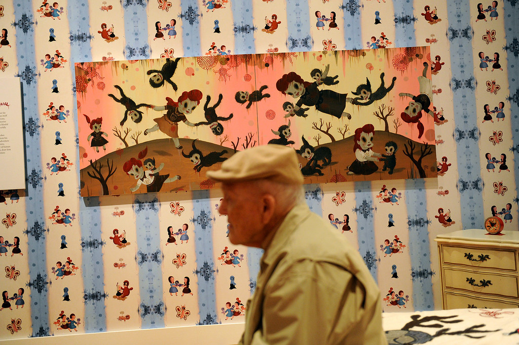 """. Jay Segal sits on the bed in the bedroom in the exhibition \""""Gary Baseman: The Door is Always Open,\"""" at the Skirball Cultural Center, Wednesday, April 24, 2013. Baseman\'s work is known for his vibrant, cartoon-like, artistic style in publications such as The New Yorker, Rolling Stone and the LA Times. He designed for the game Cranium and created the animated TV series, Teacher�s Pet.The exhibition design is based on his childhood home in LA�s Fairfax district and includes family furniture and snapshots and many items of interior décor designed by the artist, including wallpaper, pillows, a chandelier and more. (Michael Owen Baker/Staff Photographer)"""