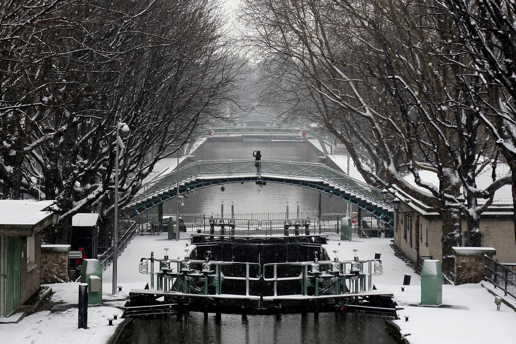 . A pedestrian takes a photo from a bridge, at the canal St Martin, in Paris, Tuesday, March 12, 2013. Hundreds of flights out of Western Europe have been cancelled, no trains running under the English Channel, and Belgium\'s prince is stuck at home, all because of a sudden dump of oddly late snowfall on Western Europe. (AP Photo/Thibault Camus)