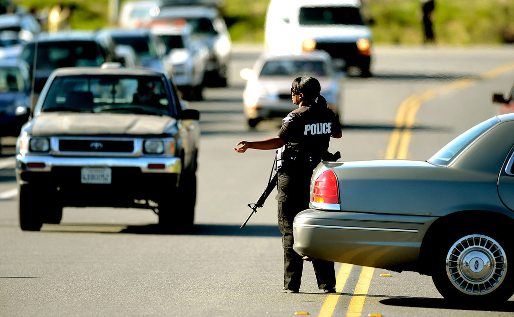 Description of . A Redlands Police officer directs traffic through a blockade at Highway 38 and Bryant Street near the Mill Street Ranger Station west of Yucaipa February 12, 2013.   Authorities believe that they exchanged gunfire with fugitive Christopher Dorner in the Angles Oaks area of the San Bernardino National Forest.  Fish and Game officers spotted a man fitting the description of Dorner driving a white pick-up, and two San Bernardino County Sheriff Deputies exchanged gunfire with him.  Authorities believe Dorner is holed up in a cabin on Glass Road and Highway 38.  GABRIEL LUIS ACOSTA/STAFF PHOTOGRAPHER.