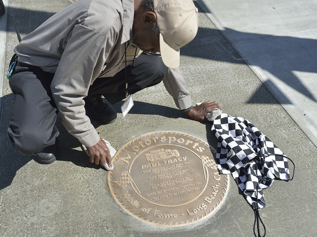 . LONG BEACH, CALIF. USA -- Hubert Moshay cleans a plaque before the start of the Long Beach (Calif.) Motorsports Grand Prix Walk of Fame induction ceremony on April 18, 2013. This year include Paul Tracy of Canada and Adrian Fernandez of Mexico. The annual Long Beach Motorsports Walk of Fame induction ceremony occurs in April of each year the Thursday before Toyota Grand Prix of Long Beach race weekend. Photo by Jeff Gritchen / Los Angeles Newspaper Group