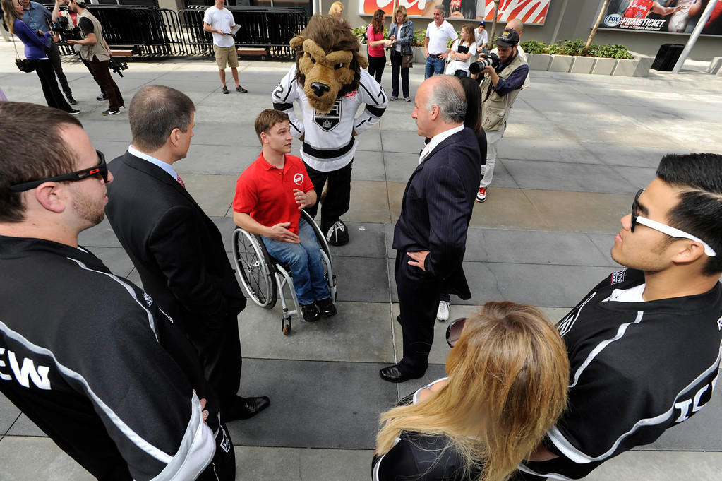 ". Ryan Chalmers talks with members of the LA Kings. Chalmers is pushing himself in a wheel chair on a coast-to-coast trip that starts at the JW Marriott in Los Angeles, and will end in New York\'s Central Park. The 3000 mile odysey will raise funds for an organization called  ""Stay Focused\"" that allows teens and young adults with disabilities to participate in sports alongsid able-bodied people.  Los Angeles CA 4/6/2013(John McCoy/Staff Photographer"
