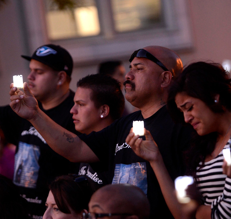 Description of . James Gonzales and niece Marisa, 19, commemorate the life of  homicide victim Gregorio Gonzales, 19, during the annual Victims Candlelight Vigil at the police station in San Bernardino April 23, 2013.   GABRIEL LUIS ACOSTA/STAFF PHOTOGRAPHER.