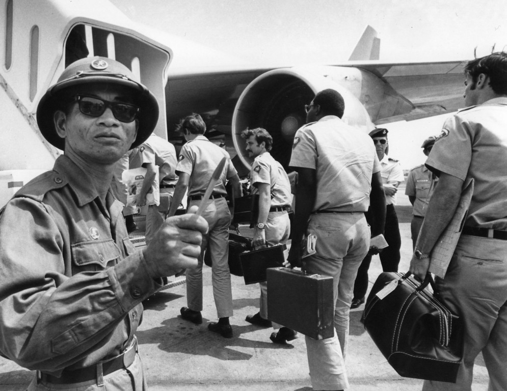 Description of . A Viet Cong observer of the Four Party Joint Military Commission counts U.S. troops as they prepare to board jet aircraft at Saigonís Tan Son Nhut airport, March 28, 1973.  Nineteen planeloads of U.S. personnel left Vietnam as the withdrawal of American troops drew to a close according to the provisions of the Paris Accords. (AP Photo/Neal Ulevich)