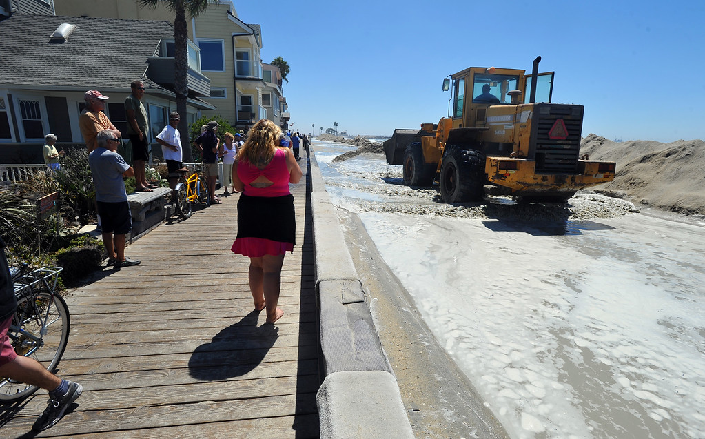 Description of . High tide and a storm surge from Hurricane Marie had locals bracing for the worst in the Peninsula neighborhood in Long Beach, CA on Wednesday, August 27, 2014. With city crews constantly building a sand berm, the water was held back from the homes and streets during the morning high tide. (Photo by Scott Varley, Daily Breeze)