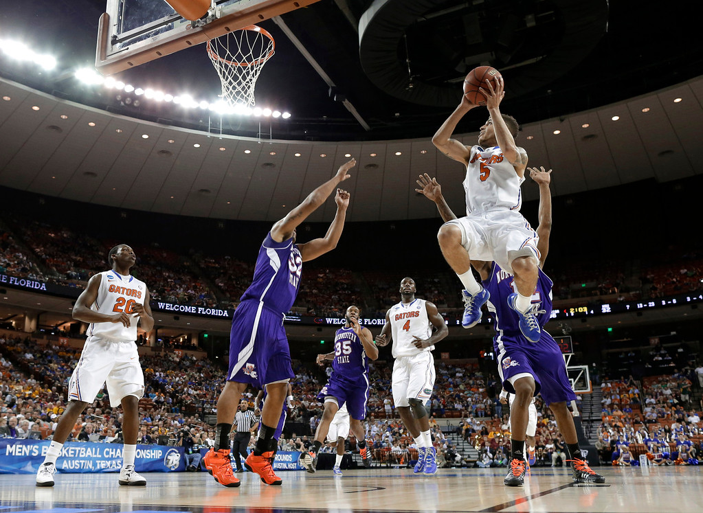 . Florida\'s Scottie Wilbekin (5) goes up for a shot as Northwestern State\'s Jalan West, obscured, and DeQuan Hicks (32) defend during the first half of a second-round game of the NCAA men\'s college basketball tournament Friday, March 22, 2013, in Austin, Texas. (AP Photo/David J. Phillip)