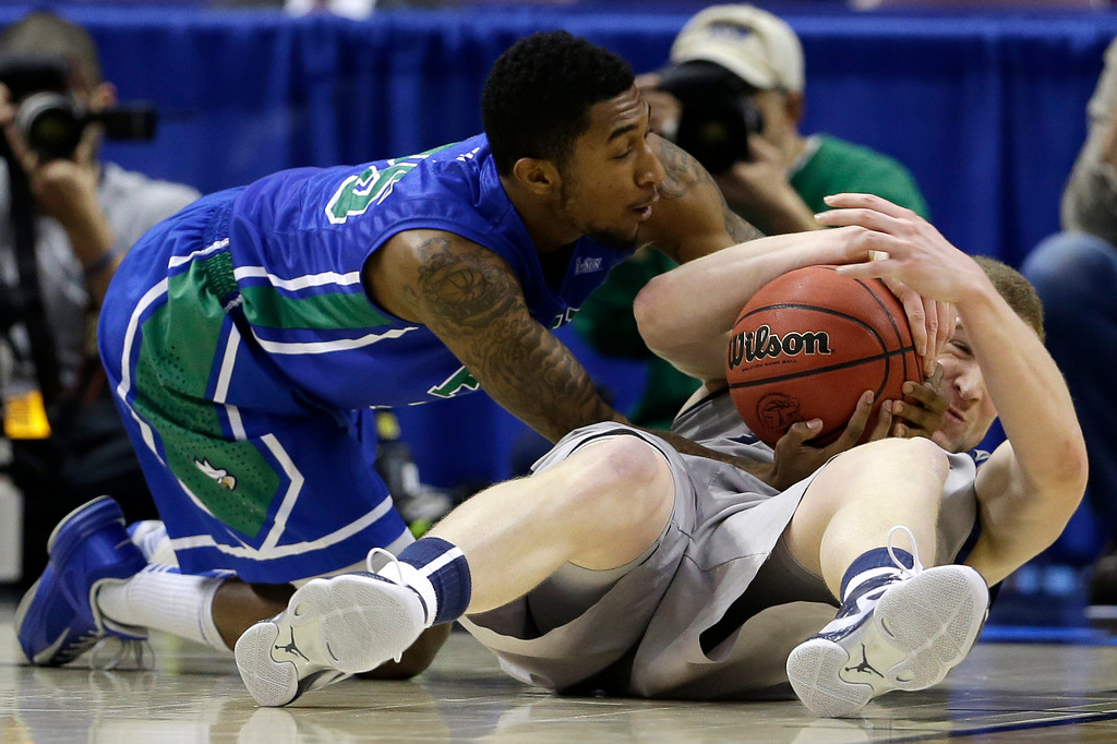 . Florida Gulf Coast\'s Dajuan Graf, left, struggles for a loose ball with Georgetown\'s Nate Lubick during the first half of a second-round game of the NCAA college basketball tournament on Friday, March 22, 2013, in Philadelphia. (AP Photo/Matt Rourke)