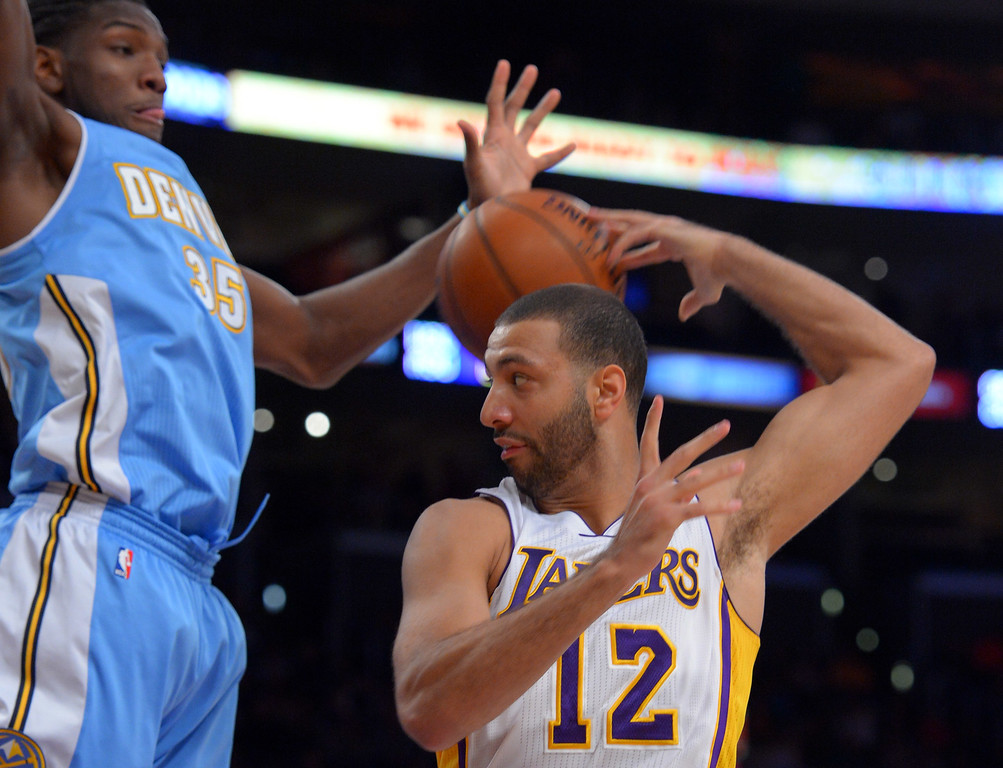. Lakers Kendall Marshall makes an errant pass behind his head as Nuggets\' Kenneth Faried defends him under the basket at the Staple Center in Los Angeles, CA on Sunday, January 5, 2014. 1st half.  (Photo by Scott Varley, Daily Breeze)